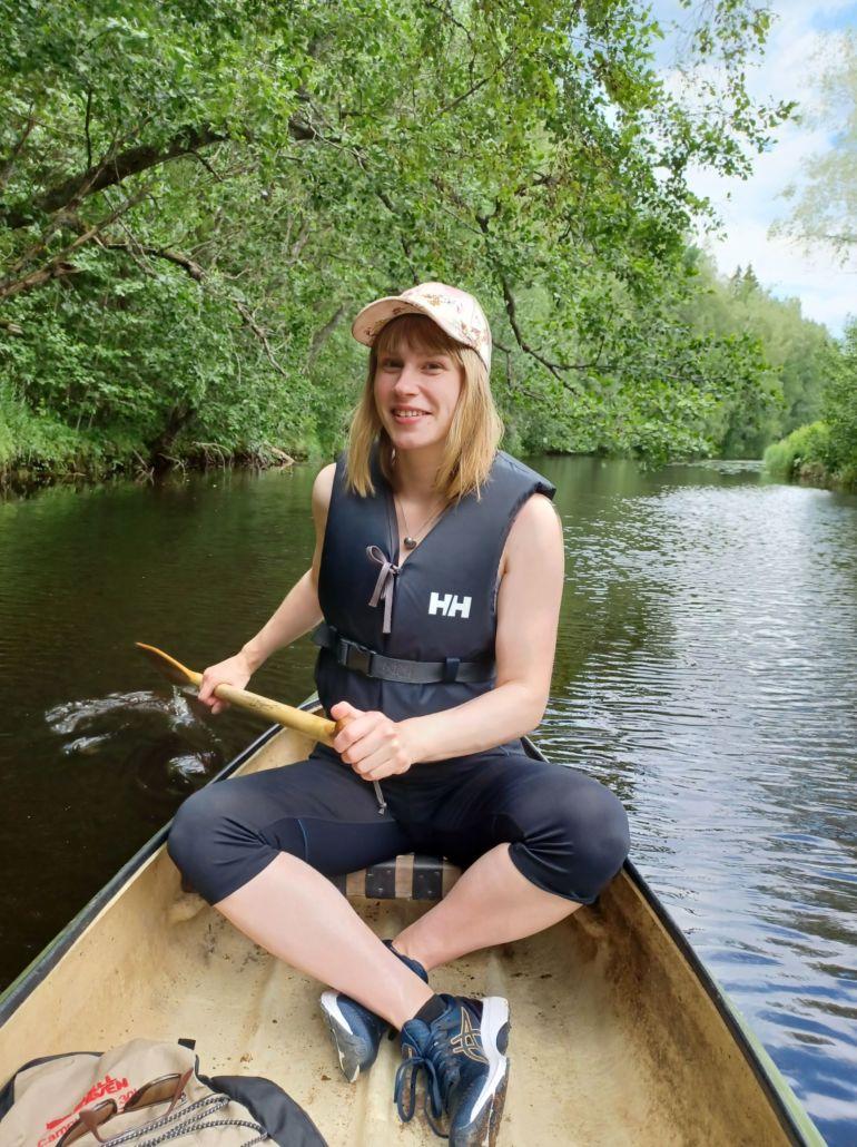 Nainen hymyilee ja istuu melomassa kanootissa. Taustalla joen pinta on tasainen, mutta väreilee hieman ja joen varressa on vehreitä puita.