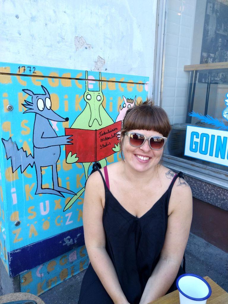 Kuvassa Laura paistattelee päivää takanaan koristemaalaus